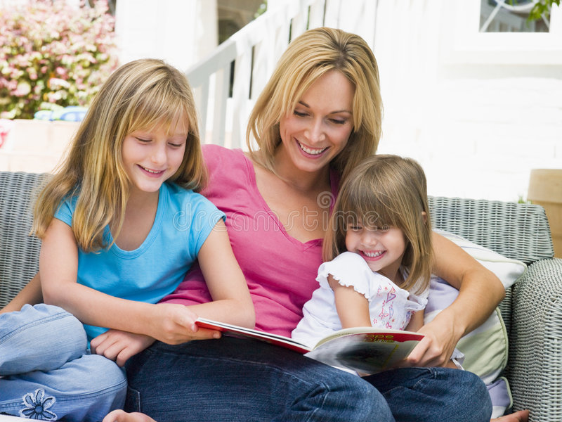 Woman and two young girls sitting on patio reading stock photos