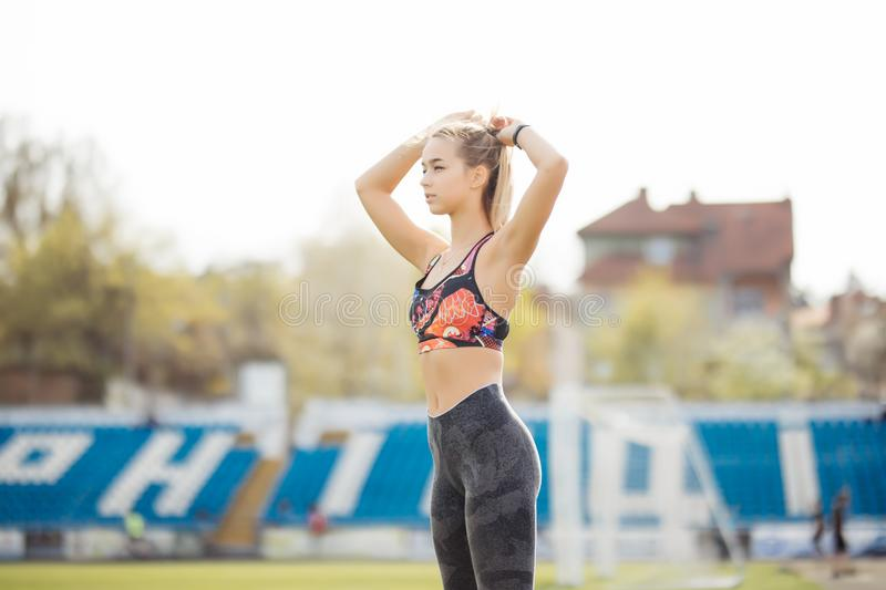 Woman tying hair in ponytail getting ready for exercising. Beautiful young sporty woman attaching her long hair at stadium. Smilin royalty free stock photos