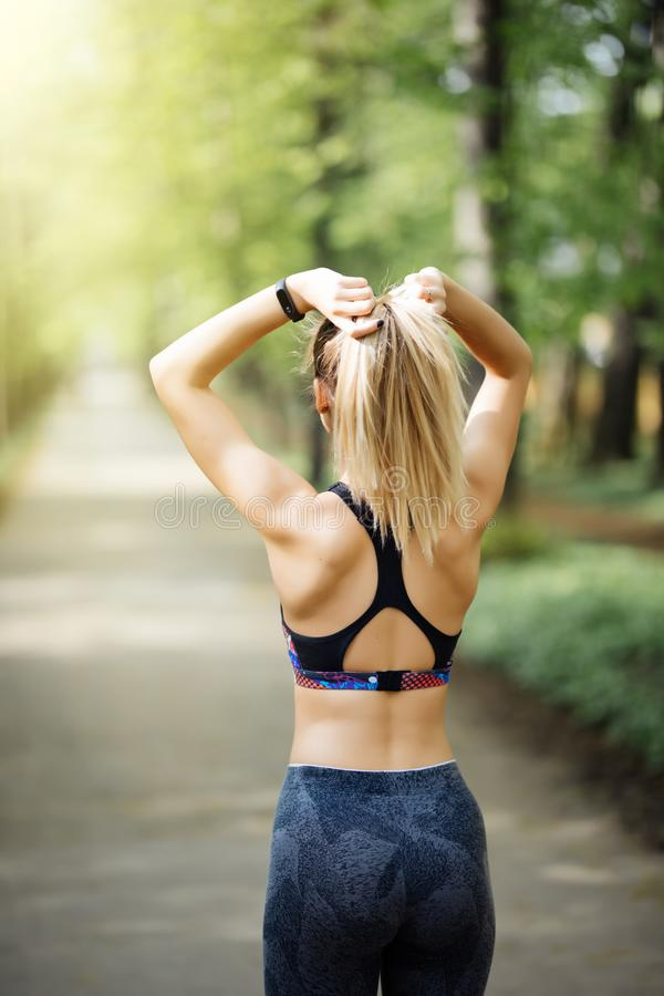 Woman tying hair in ponytail getting ready for exercising at sunset. Beautiful young sporty woman attaching her long hair in park. royalty free stock image