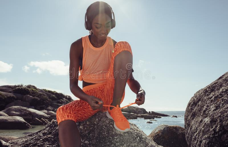 Woman tying her shoe laces before a run at beach stock photography