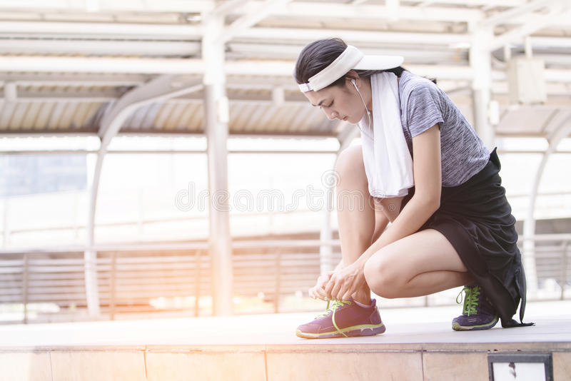 Woman tying running shoes getting ready for jogging stock image