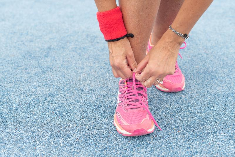 Woman tying running shoes lace in the park outdoor stock image