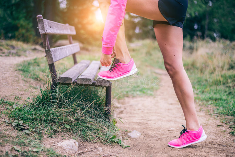 Woman tying running shoes stock image