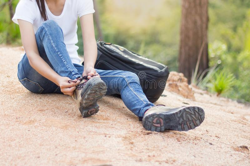 Woman tying shoe laces, Closeup of female tourist getting ready. For hiking, Hiking shoes stock photography