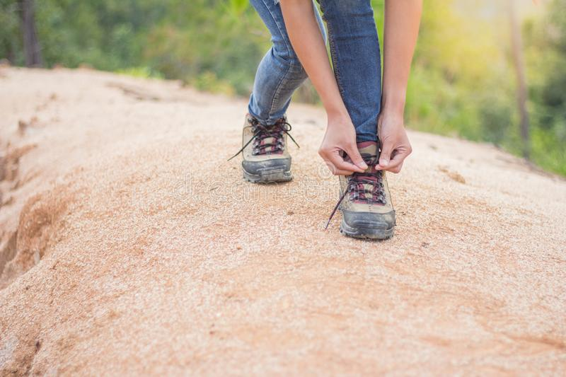 Woman tying shoe laces, Closeup of female tourist getting ready. For hiking, Hiking shoes royalty free stock photo
