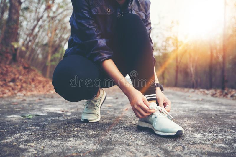 woman tying shoe laces for sport fitness runner getting ready for jogging outdoors on forest path in late summer or fall. stock images