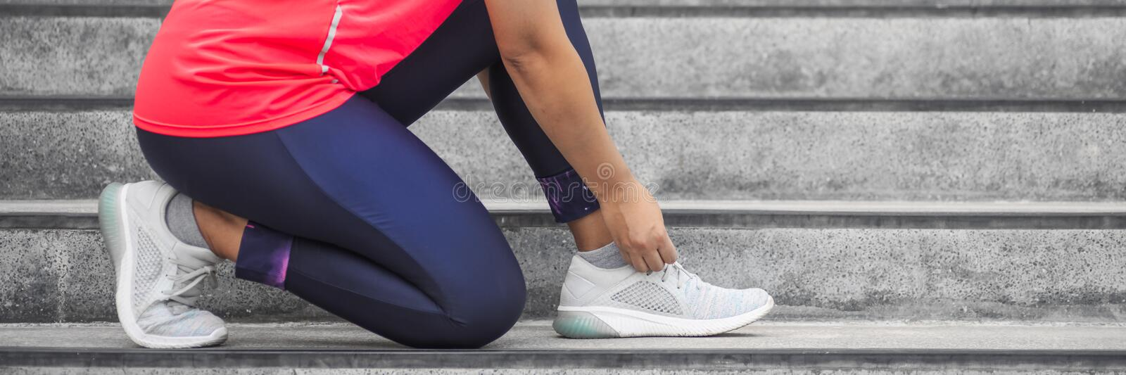 Woman tying shoelace on running shoes before practice. Runner getting ready for training. Sport active lifestyle concept.  Outdoor stock photo