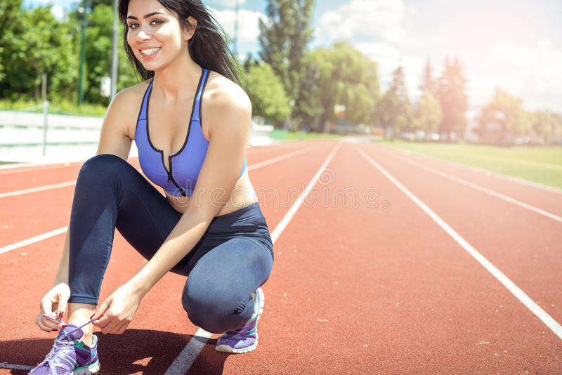 Woman tying shoes on running track. Young adult fitness woman tying shoes on athletic track while preparing for training. Toned image stock photography