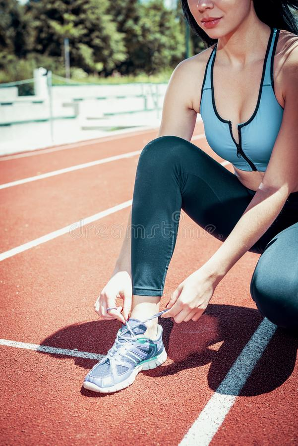 Woman tying shoes on running track. Young adult fitness woman tying shoes on athletic track while preparing for training. Toned image stock images