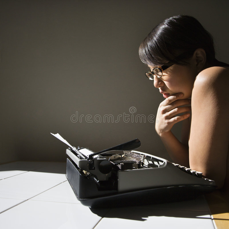 Woman with typewriter. Nude young Asian woman sitting at kitchen table reading paper in typewriter royalty free stock photos
