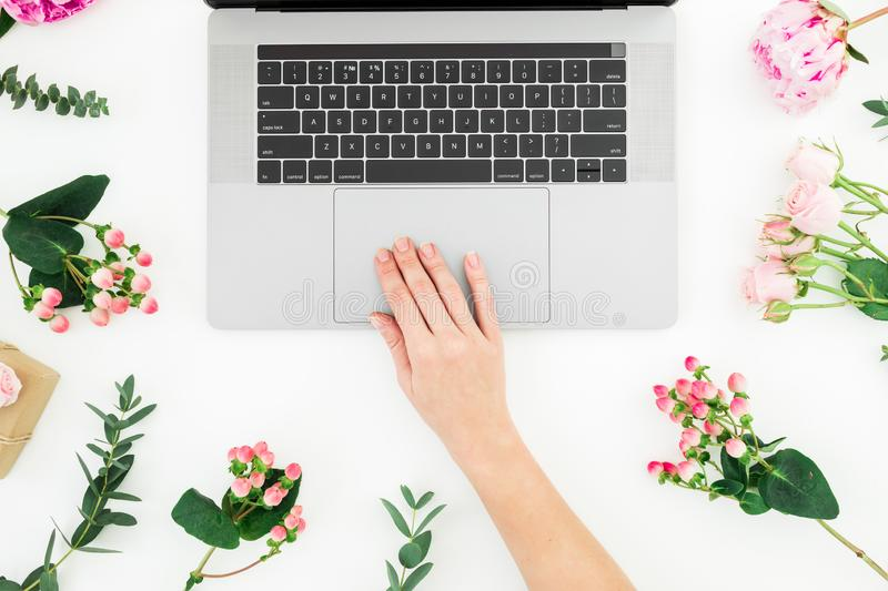 Woman typing on laptop. Beautiful workspace with female hands, laptop, notebook and pink flowers on white background. Top view. Fl stock photo