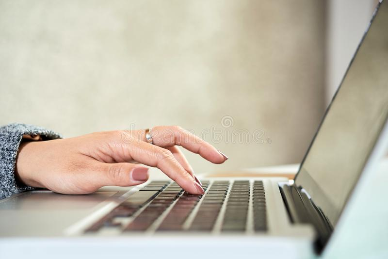 Woman typing on laptop stock images