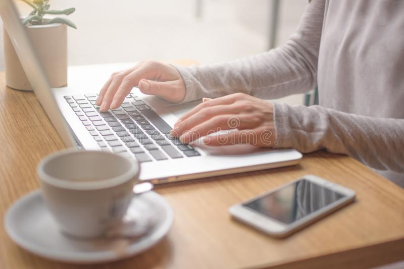 Woman typing on laptop computer and using smart phone royalty free stock photography