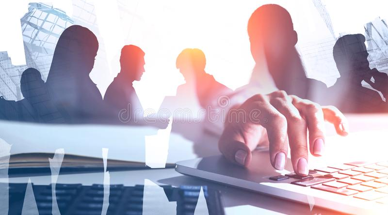 Woman typing on laptop and her team in city stock photo