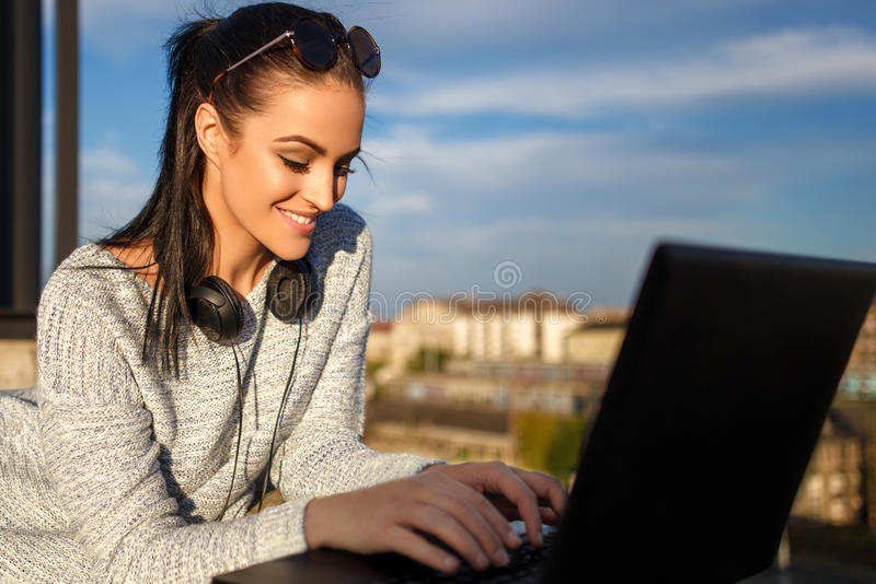 Woman typing message on laptop outdoor. In city royalty free stock images