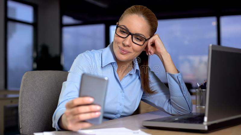 Woman typing message on mobile phone instead of working, bored at unloved job. Stock photo stock photography
