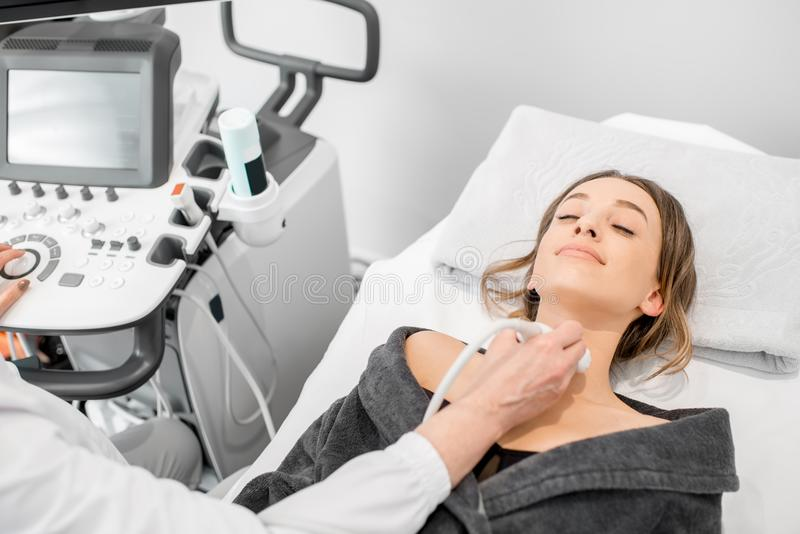 Woman during the ultrasound examination. Young woman patient during the ultrasound examination of a thyroid lying on the couch in medical office stock photos