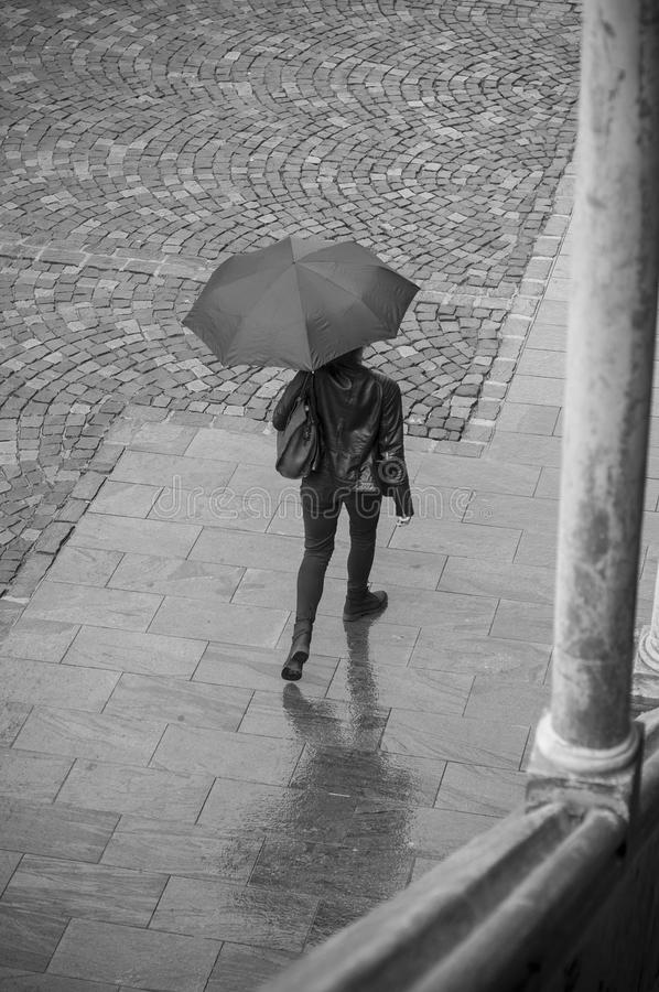 Woman with umbrella on cobbles place stock photos