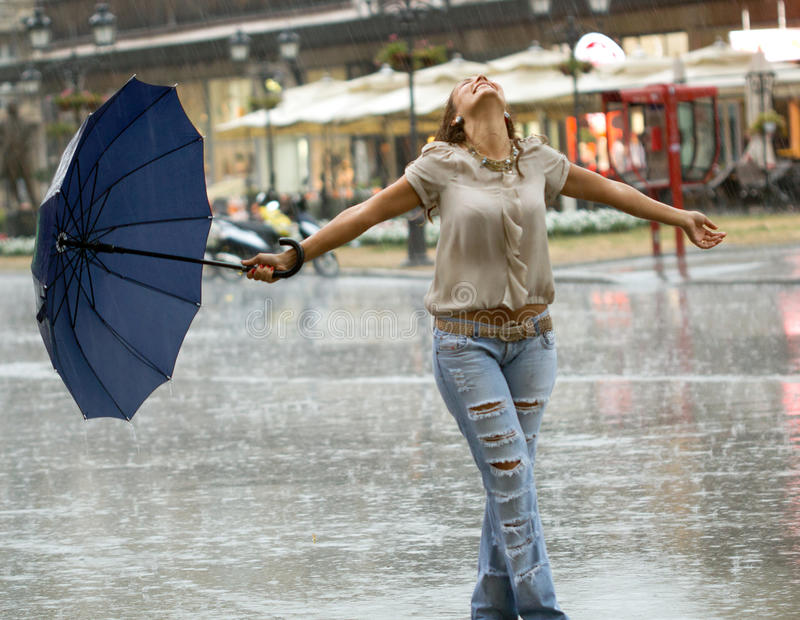 Woman with umbrella enjoying in the rain. Smiling woman with umbrella enjoying in the rain stock photo