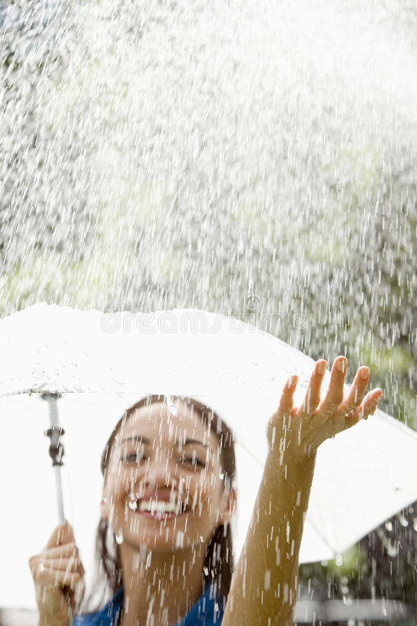 Woman with umbrella in the rain. Beautiful Hispanic woman holding umbrella out in the rain stock photo