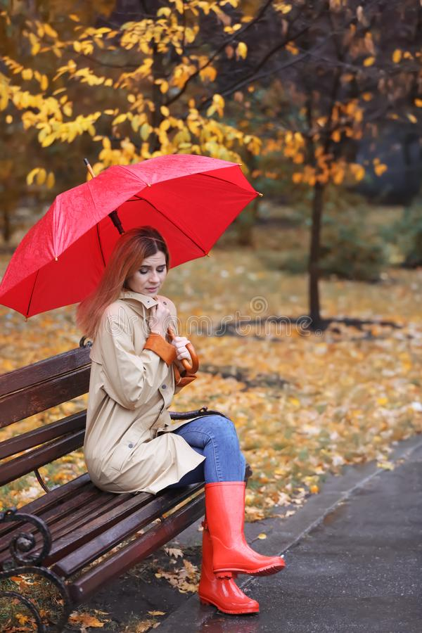Woman with umbrella sitting on bench in autumn park royalty free stock image