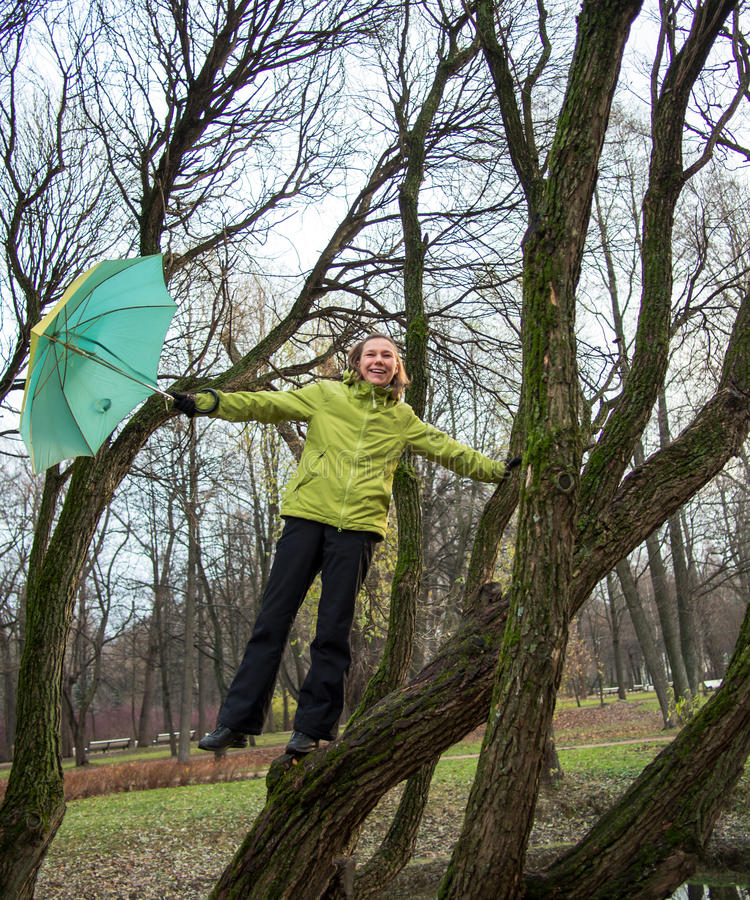 Woman with an umbrella stands on a tree stock photos