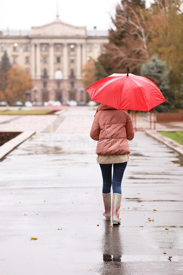 Woman with umbrella taking autumn walk in city royalty free stock photos
