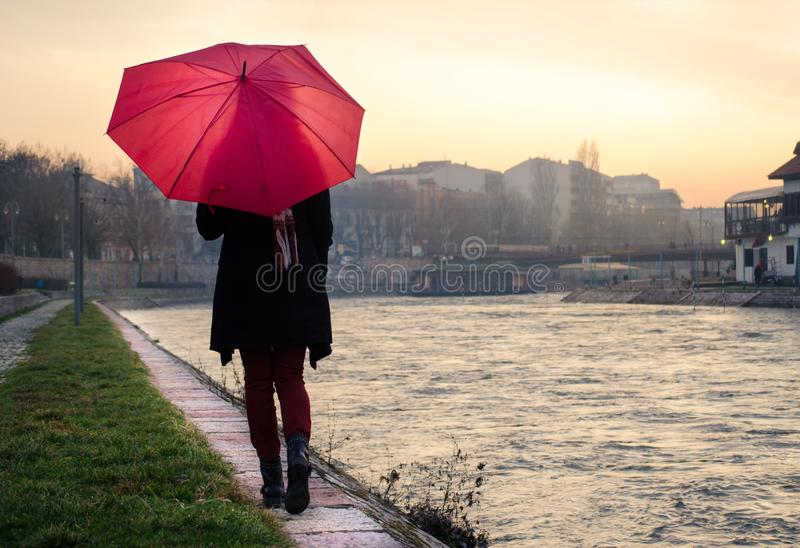 Woman with umbrella walking by the river. At sunset