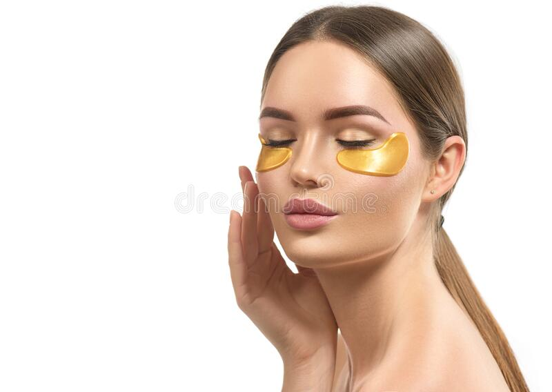 Woman with under eye collagen gold pads, beauty model girl face with healthy fresh skin. Skin care concept, anti-aging mask royalty free stock photos