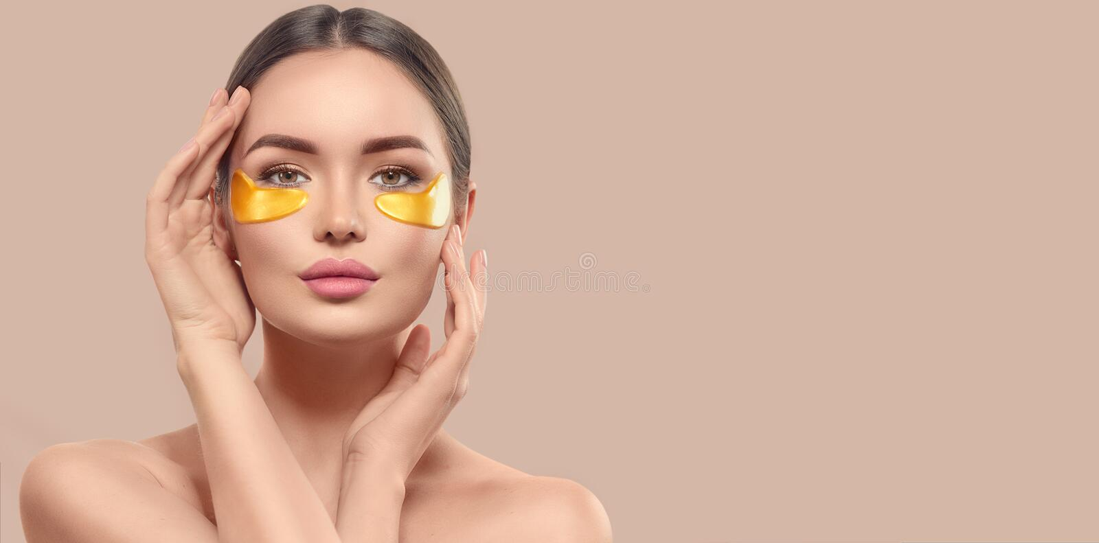 Woman with under eye collagen gold pads, beauty model girl face with healthy fresh skin. Skin care concept, anti-aging mask royalty free stock photo