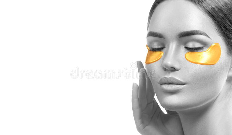 Woman with under eye collagen gold pads, beauty model girl face with healthy fresh skin. Skin care concept, anti-aging mask stock photography