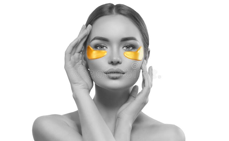 Woman with under eye collagen gold pads, beauty model girl face with healthy fresh skin. Skin care concept, anti-aging mask stock image