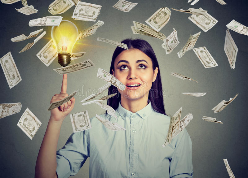 Woman under money rain pointing up at idea light bulb royalty free stock image