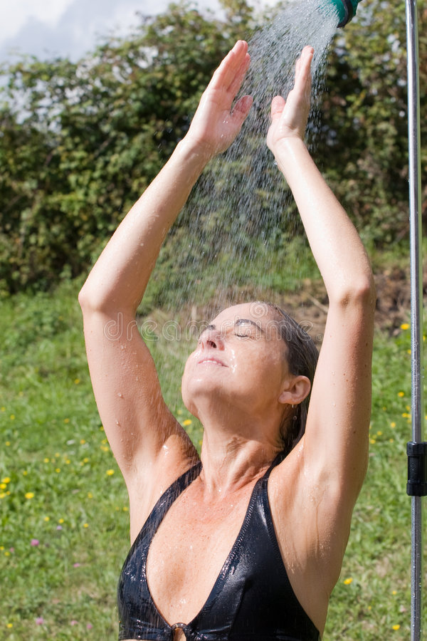 Woman under the outdoor shower stock photos
