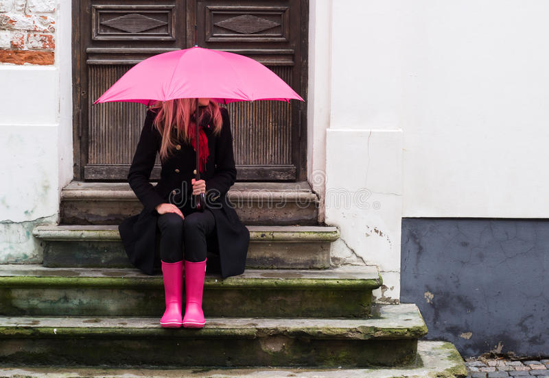Woman under pink umbrella. Is sitting on stairs in front of a house royalty free stock photo
