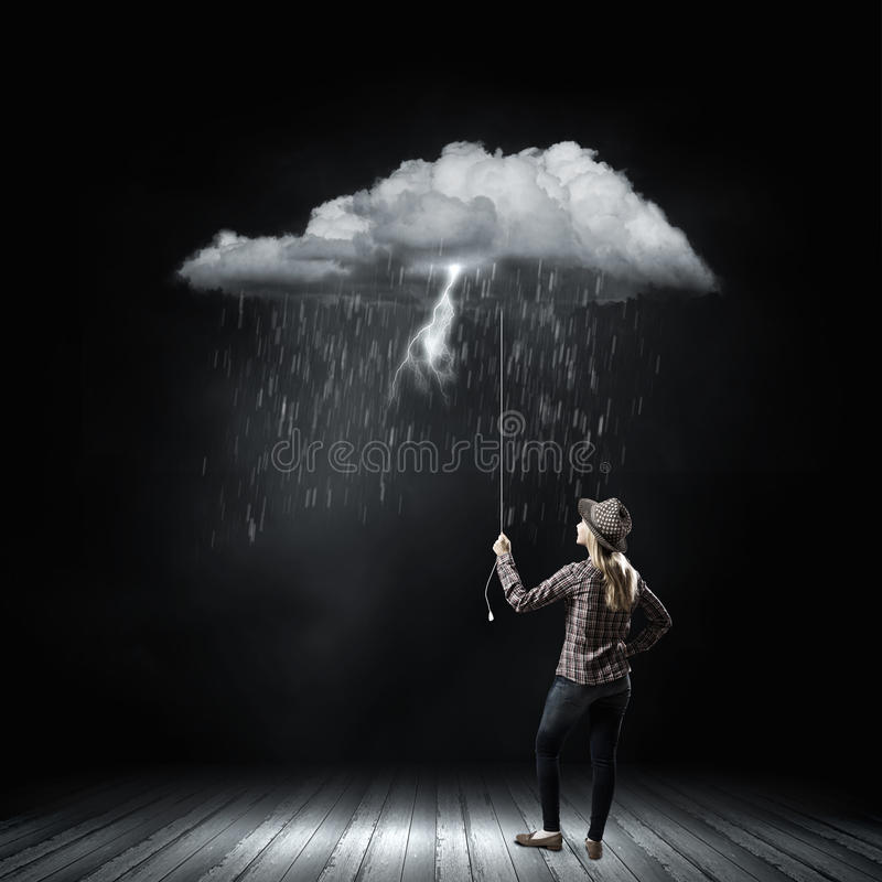 Woman under rain. Young woman in casual holding raining cloud on rope royalty free stock photography