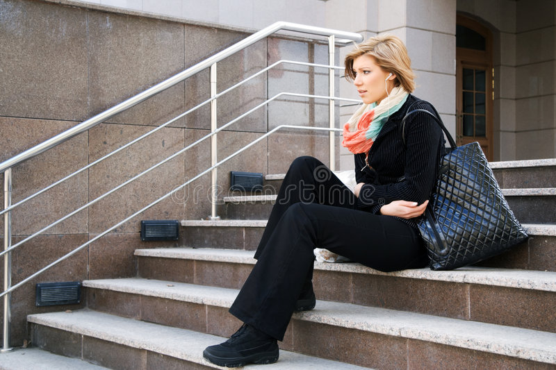 Young fashion woman in depression on the steps royalty free stock photos
