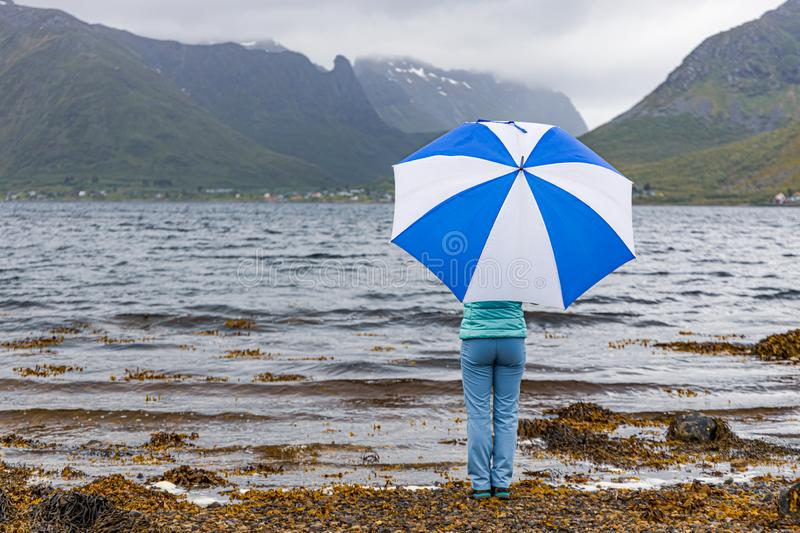 Woman under an umbrella in the background of nature Norway stock images