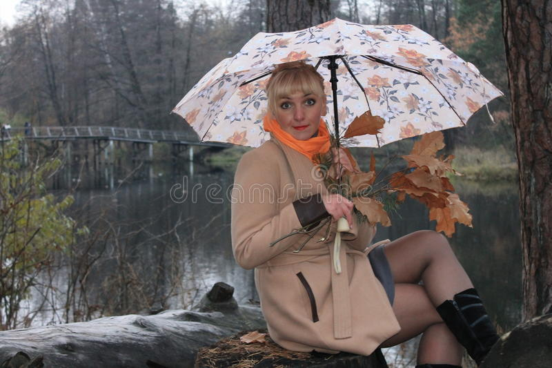 Woman under an umbrella, late fall, forest lake stock image