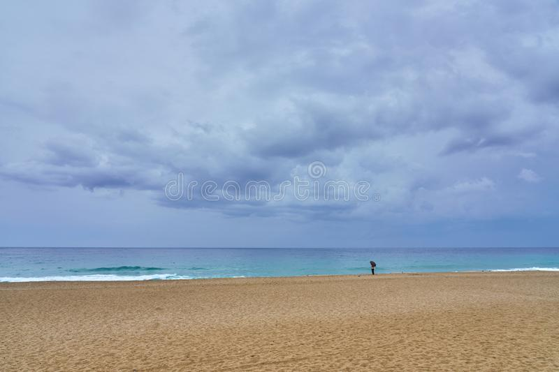 A woman under umbrella on the sandy beach looking at the water under cloudy sky. A woman under umbrella on the sandy beach looking at the water under cloudy sky royalty free stock image