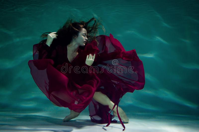 Woman under the water in a red dress. stock image