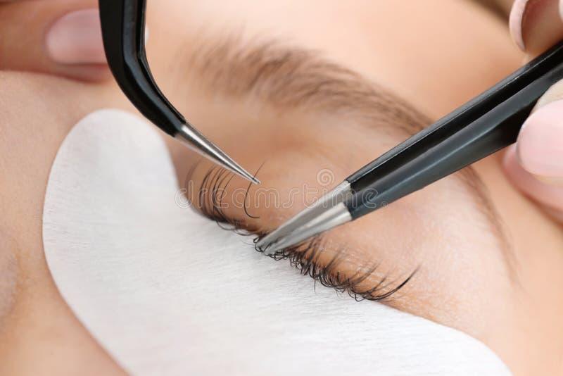 Woman undergoing eyelash extensions procedure, closeup. Young woman undergoing eyelash extensions procedure, closeup stock photo