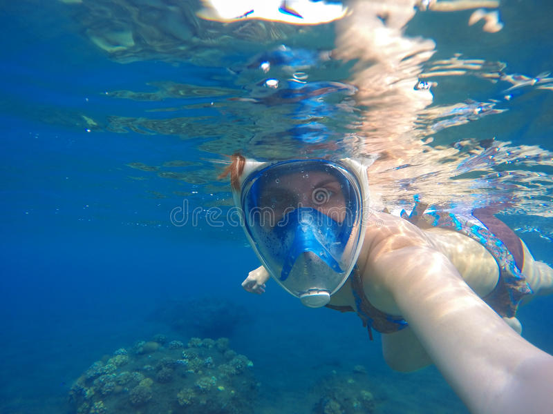 Woman underwater in full face snorkeling mask. stock photography