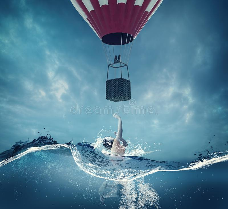 Woman underwater looking up to a balloon. royalty free stock photography
