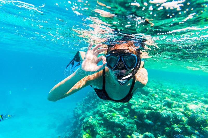 Woman underwater snorkeling with okay sign swimming in sea stock photos