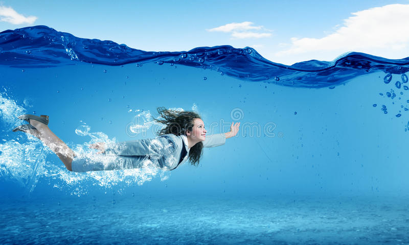 Woman underwater. Young businesswoman in suit swimming in crystal blue water