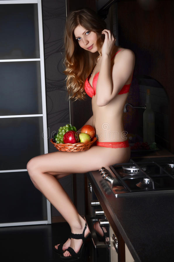 Woman in underwear with a basket of fruit on kitchen royalty free stock photos