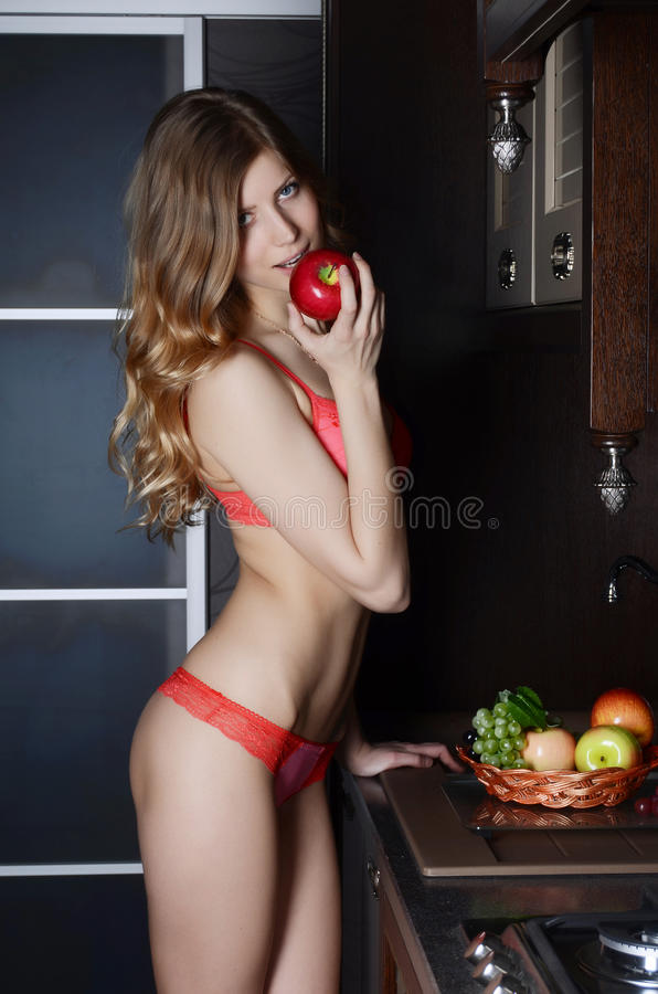 Woman in underwear with a basket of fruit on kitchen stock photo