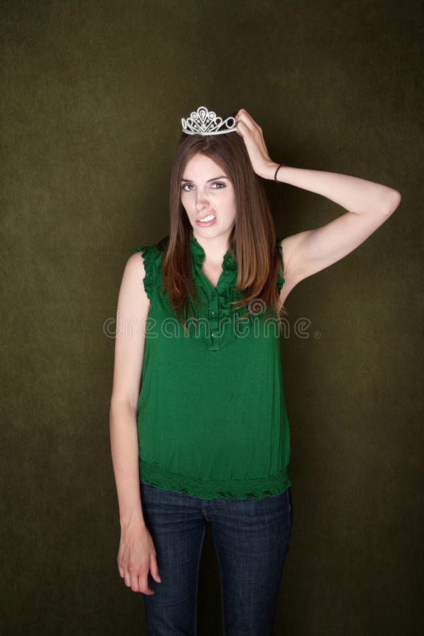Woman Unhappy With Her Tiara. Caucasian woman sneers while adjusting her crown royalty free stock photography