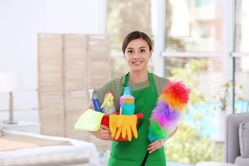 Woman in uniform with cleaning supplies. Indoors royalty free stock image